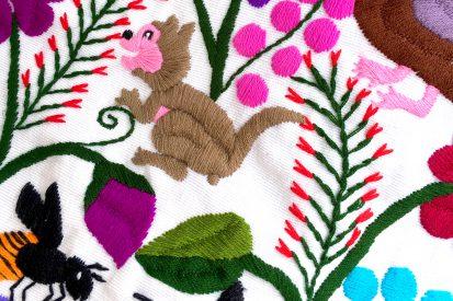 Embroidered textile from Chiapas, Mexico depicting flor de bótil.